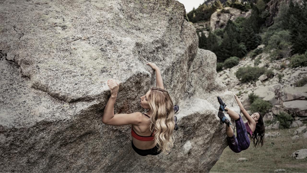 Women practicing boulder rock climbing