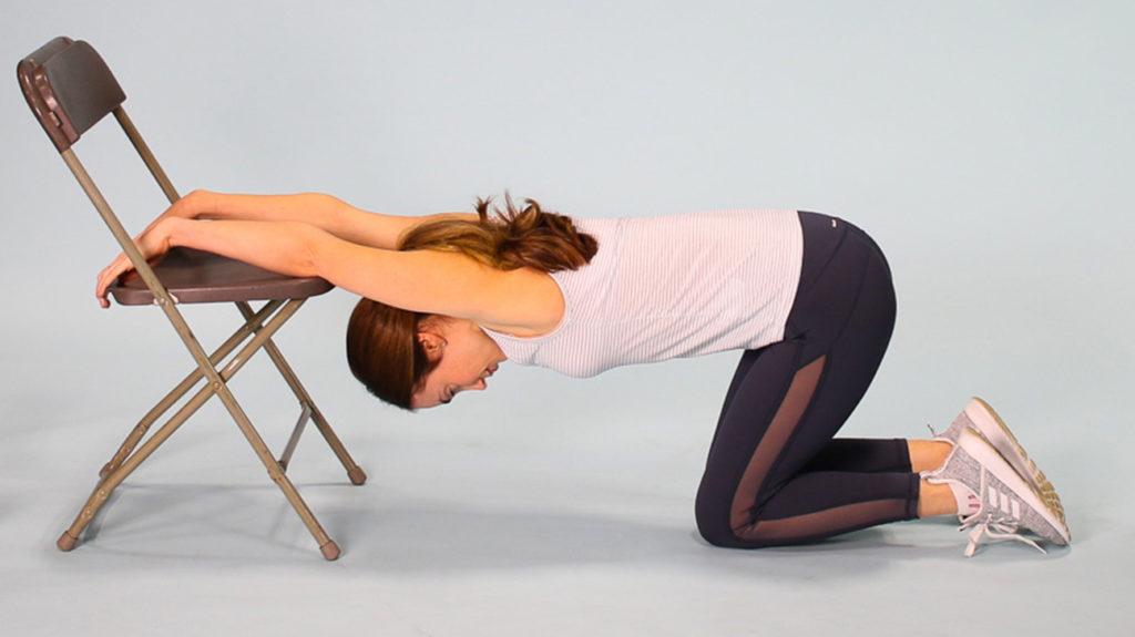 Woman demonstrating lat climbing stretch